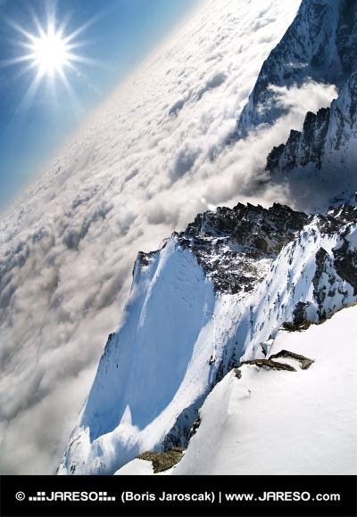 Над облаците Lomnicky връх с лъчи на слънцето