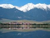 Kleines Dorf unter riesigen Bergen