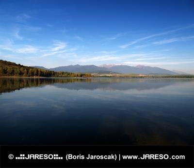 Montañas de Rohace reflejan en las aguas de Liptovska Mara durante la puesta del sol