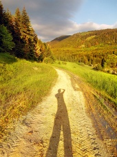 Carretera al atardecer con una larga sombra