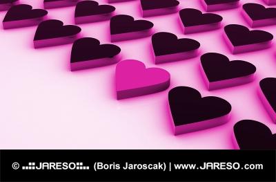 Un coeur rose entre un grand nombre de coeurs noirs