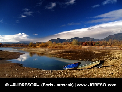 Vue d'automne de deux bateaux et le lac en jour nuageux