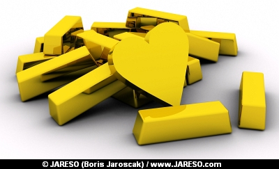 Golden heart near pile of gold bars