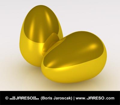 Due uova d'oro su sfondo bianco