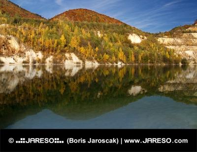 Reflectie van de herfst heuvels in Sutovo meer, Slowakije