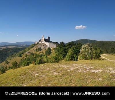 Cachtice kasteel op de heuvel in de verte