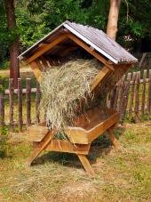 Beschutte houten feeder volledig gevuld met hooi