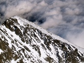 Close up of snowy Lomnicky peak and clouds from above