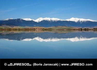 Reflektion av snöiga Roháče berg