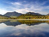 Kullar ?terspeglas i Liptovska Mara Lake vid solnedg?ngen