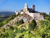 Ruinerna av slottet Cachtice gömd i grön skog