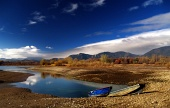 Autumn view of two boats and lake in cloudy day