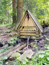 Wooden cabin with natural water stream in the forest